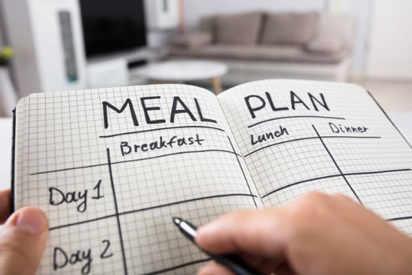 Writing in meal plan notebook