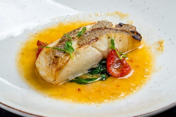 Large halibut steak on plat with tomatoes