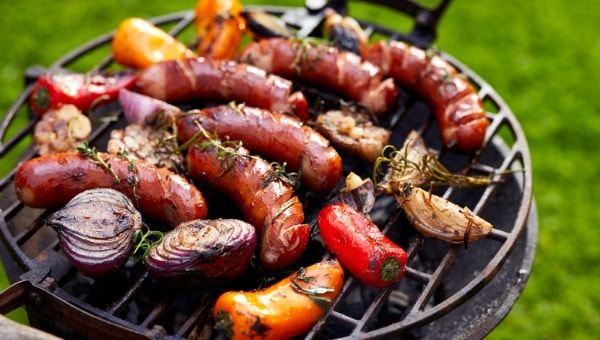 Brats cooking on grill with vegetables and peppers