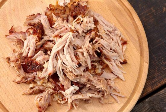 Shredded pork on cutting board