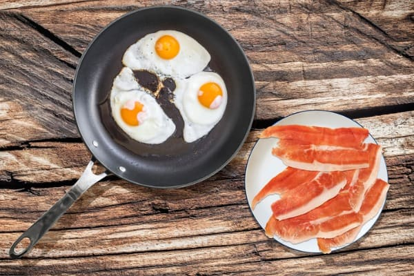 couple of sunny side up fried eggs in large frying pan