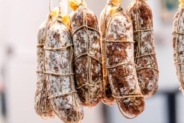 salami rolls sausages hanging on string