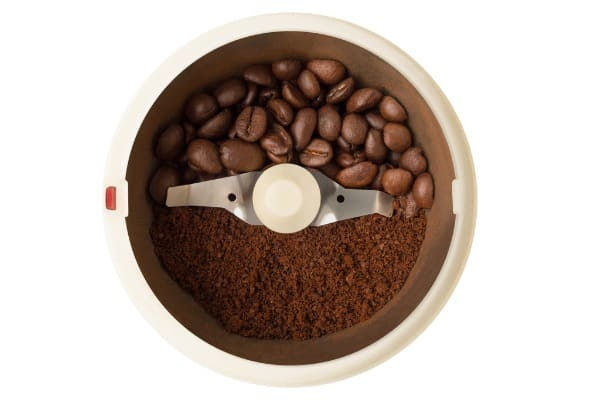 coffee grinder with halves of whole and ground beans
