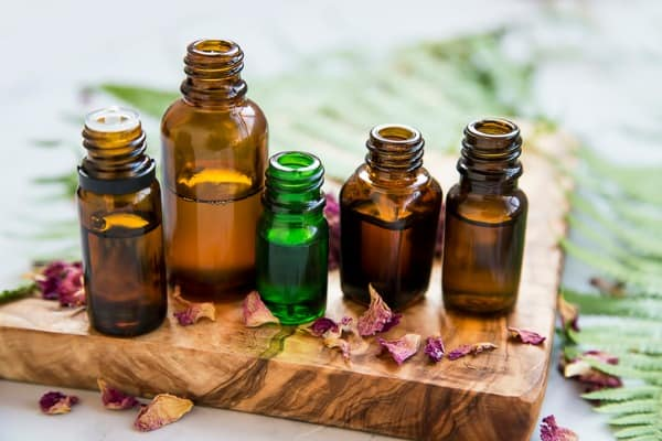 aromatherapy oil bottles with flowers and green leaves for sprained ankle