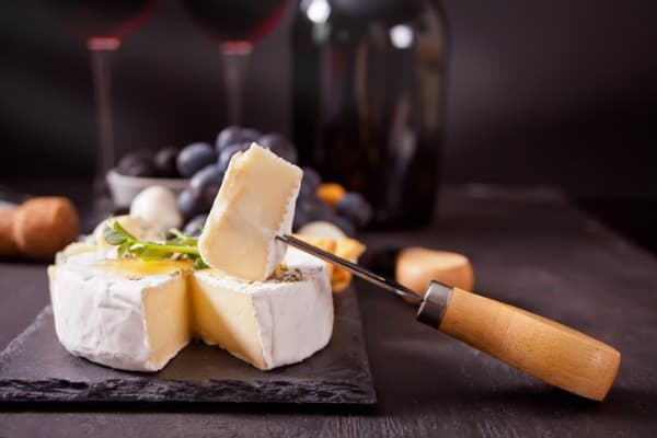 cheese camembert brie on the board two glasses and bottle of red wine