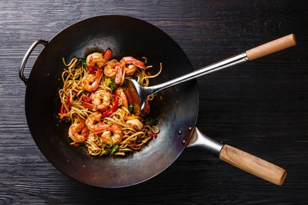 udon stirfry noodles with shrimp and vegetables in wok pan