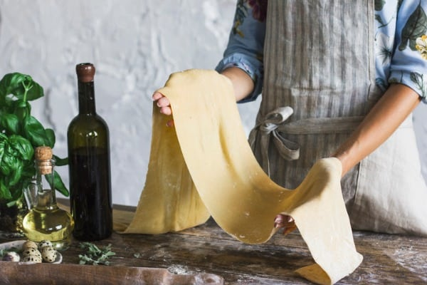 young woman in apron holding the dough for homemade pasta at rustic